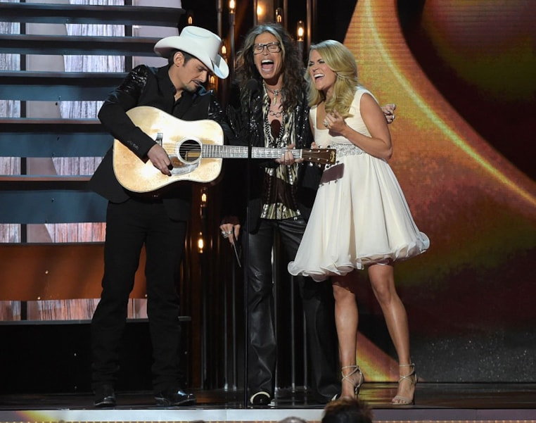 NASHVILLE, TN - NOVEMBER 05:  Brad Paisley, Steven Tyler, and Carrie Underwood speak onstage during the 48th annual CMA awards at the Bridgestone Arena on November 5, 2014 in Nashville, Tennessee.  (Photo by Rick Diamond/Getty Images)